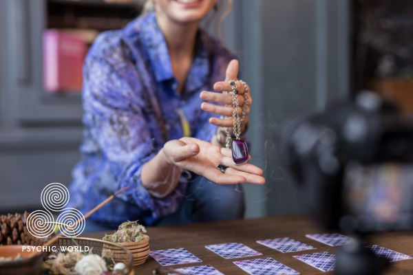 woman holding a crystal to read tarot cards