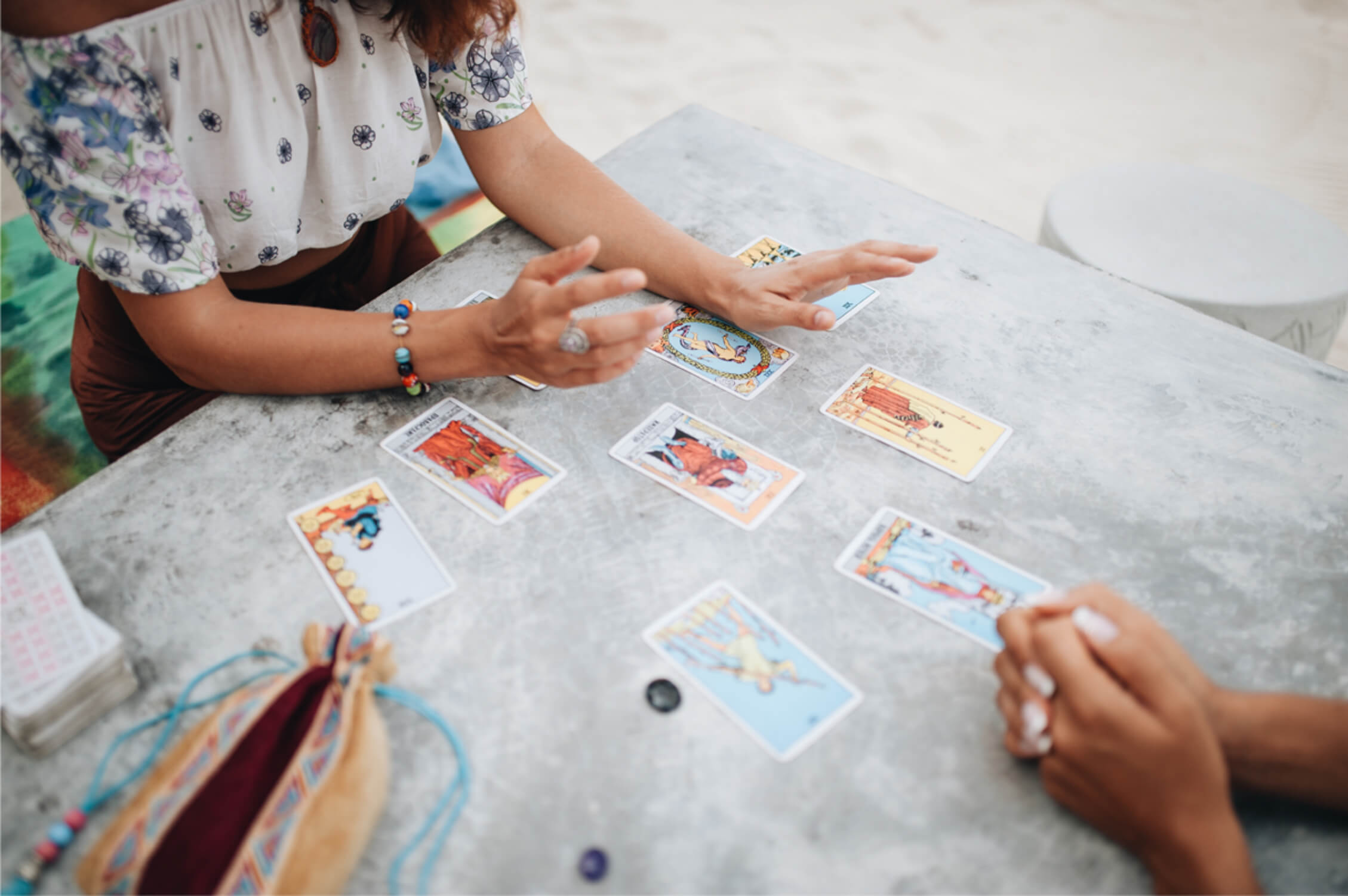 women reading tarot outside on a beach