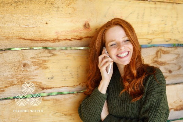 woman with green shirt smiling on the phone