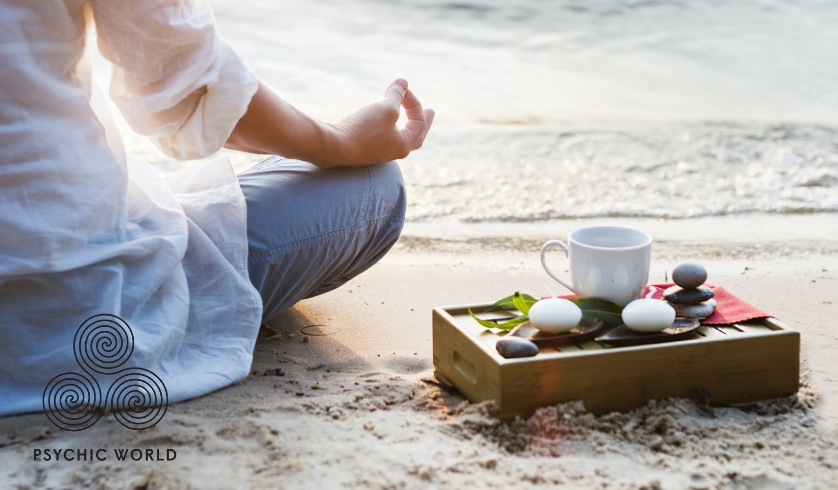 woman meditating on the sand drinking tea
